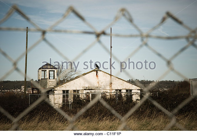 Abandoned building through fencing - Stock Image