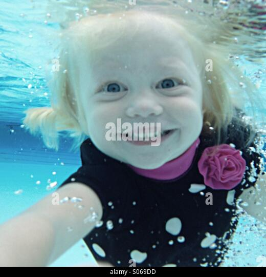 Young girl smiling as she swims towards camera underwater. - Stock Image
