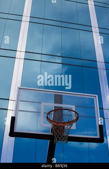Basketball hoop with glass backboard in front of sleek glass modern office building reflecting clouds in the surface - Stock Image