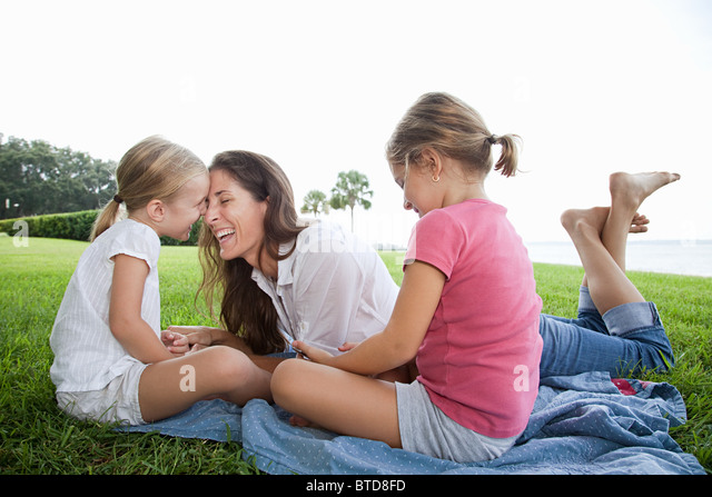 Happy mother and daughters lying on grass - Stock Image