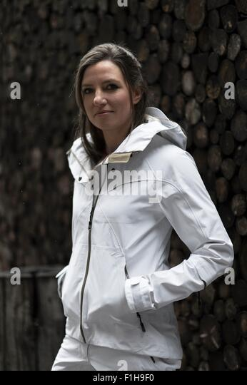 Mid adult woman wearing white coat, portrait - Stock Image