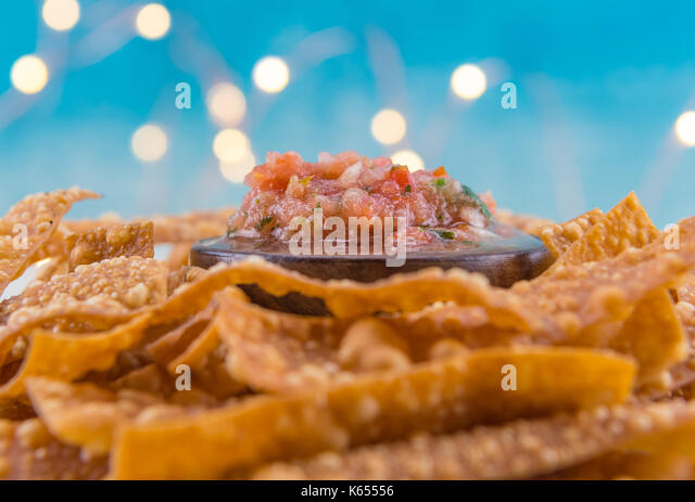 Selective Focus on Bowl of Salsa on Bed of Chips with bokeh in background - Stock Image