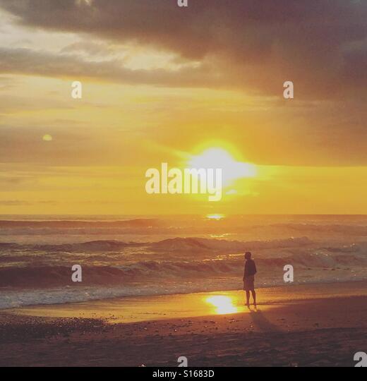 A man watching the sunset at Playa El Carmen, on the Nicoya Peninsula, Costa Rica - Stock-Bilder