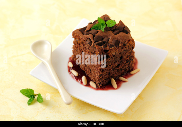 Brownie with cherry jam and pine nuts. Recipe available. - Stock Image