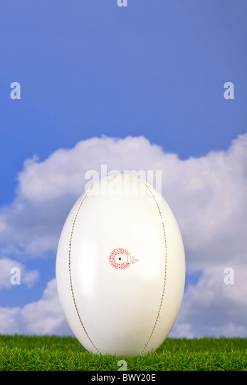 Photo of a rugby ball tee'd up on grass with sky background. - Stock Image