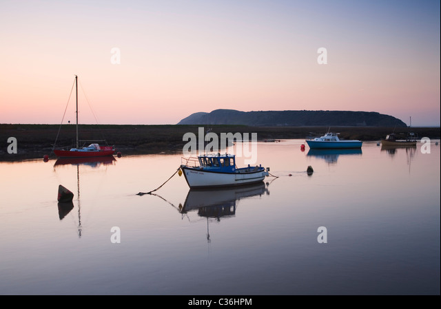 Boats moored on the River Axe with Brean Down in the distance. Somerset. England. UK. - Stock Image
