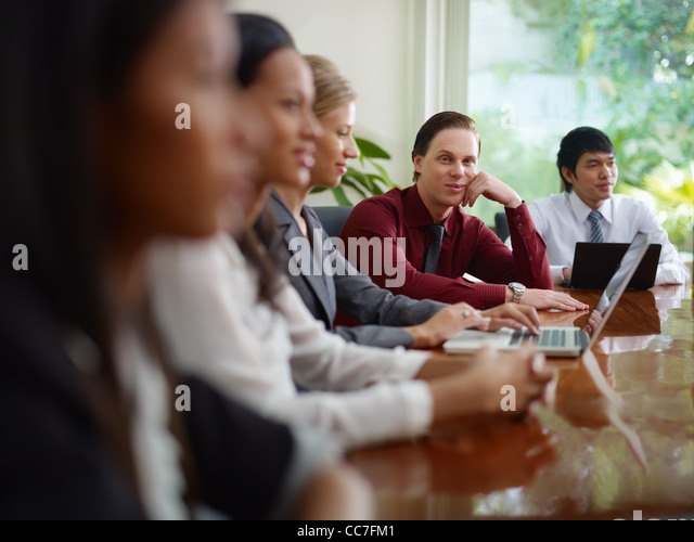 young business man working as manager and smiling at camera during meeting with colleagues - Stock Image