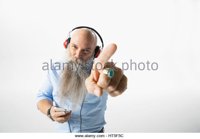 Portrait cool hipster businessman with beard pointing, listening to music with headphones against white background - Stock-Bilder