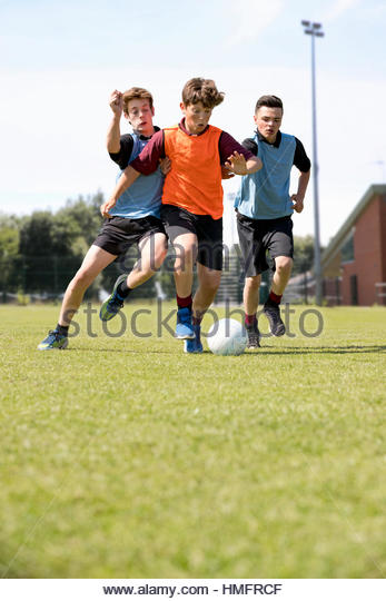 Middle schoolboys running playing soccer on field in physical education class - Stock-Bilder