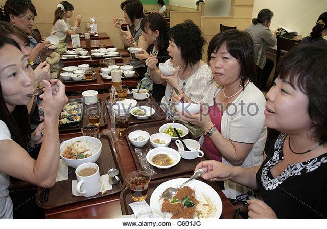 Tokyo Japan Shinjuku Shinjuku NS Building restaurant office workers Asian woman women co-workers eating dining - Stock Image