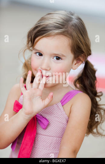 young girl licking her fingers - Stock Image