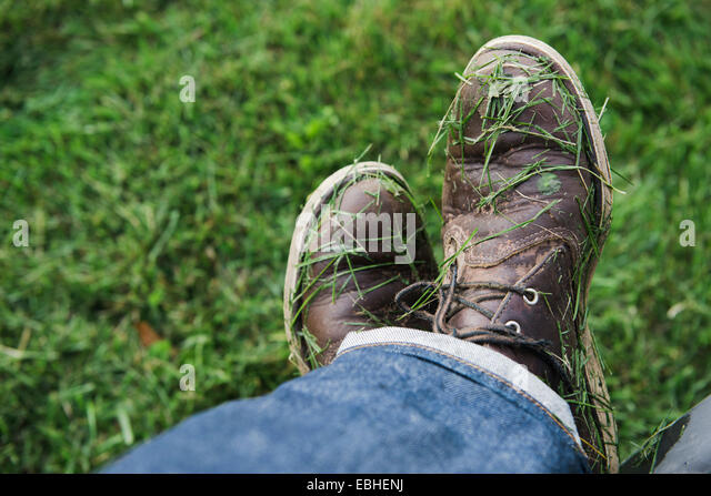Mans shoes covered in freshly mown grass - Stock Image