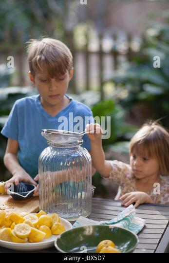 Boy and two young sister preparing lemon juice for lemonade at garden table - Stock-Bilder