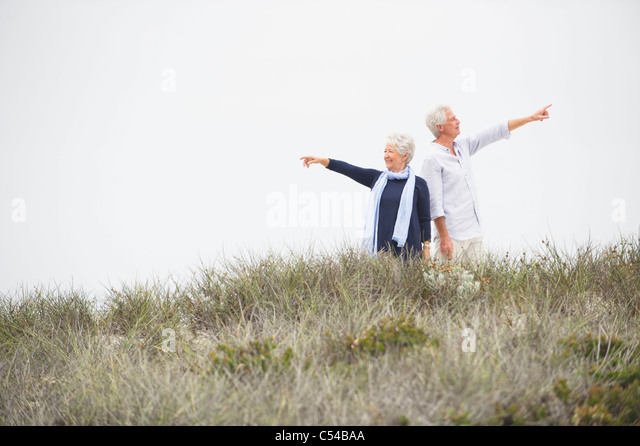 Senior couple pointing at different direction against clear sky - Stock Image
