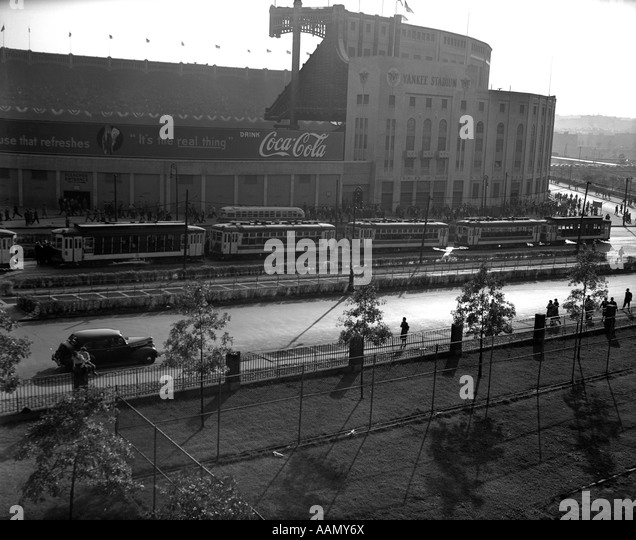 1940s EXTERIOR OF YANKEE STADIUM WITH A COCA COLA BANNER ON WALL TREE LINED STREET WITH PEDESTRIANS NYC USA - Stock Image