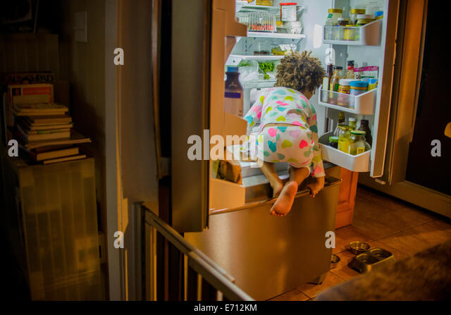 Rear view of girl sneaking food and drink from the refrigerator at night - Stock Image