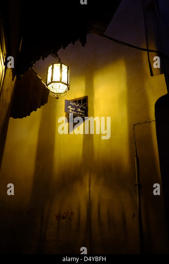 A street lamp hanging in the medina in Meknes with the pieced metal shadow highlighted against the yellow wall - Stock Image