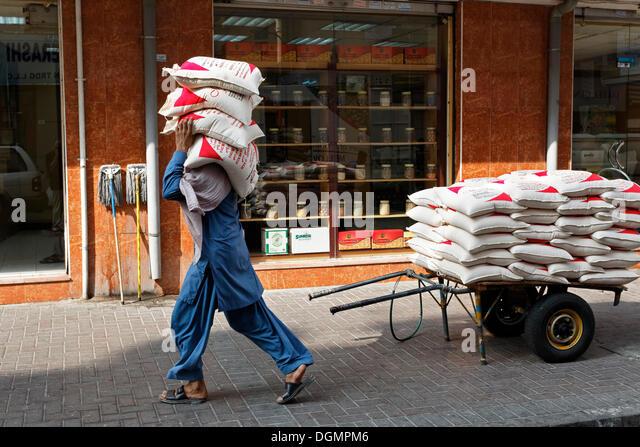Worker carrying sacks of lentils on his shoulder, Deira, Old Souk, Dubai, United Arab Emirates, Middle East - Stock-Bilder