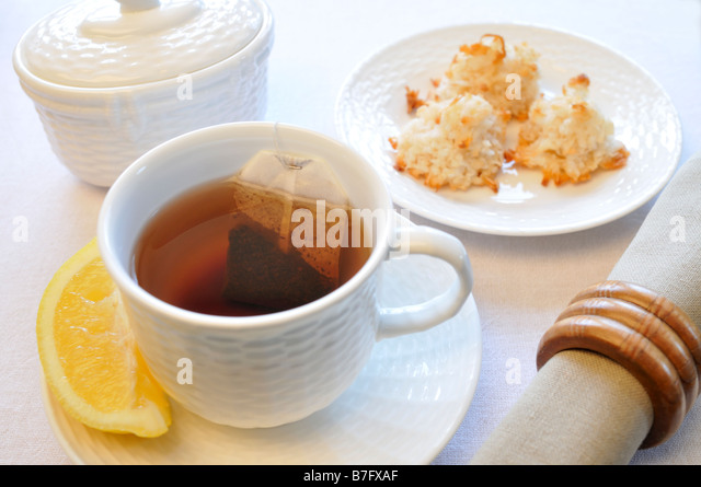 Black tea in cup with lemon coconut macaroon cookies napkin and sugar ...