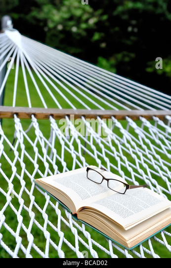 Summer reading staycation home vacation retirement weekend concept glasses eyeglasses spectacles open book backyard - Stock Image