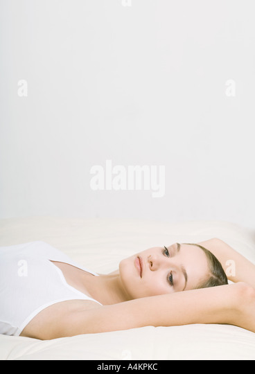 Woman lying back on bed with arms over head - Stock Image
