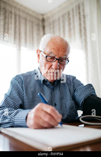 Senior man controlling his blood pressure and writing down the result - Stock Image