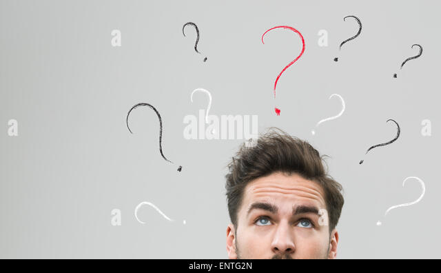 thinking man with many question marks above his head, against grey background - Stock Image
