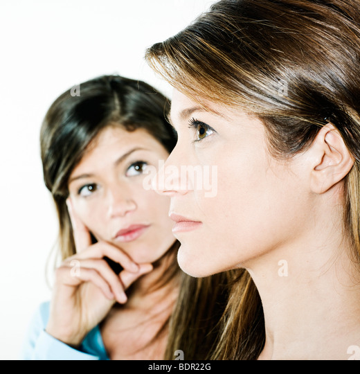 studio shot portrait on isolated background of two sisters twin women friends looking at the other as it was herself - Stock-Bilder