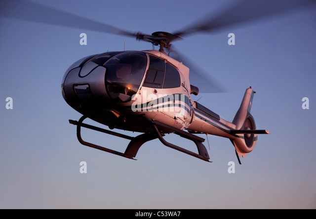 Helicopter flying in the blue sky - Stock Image