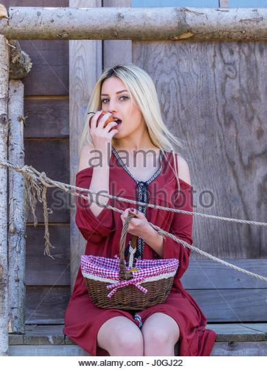 Beautiful blonde young woman basket fruit apple in hand eat eating - Stock Image
