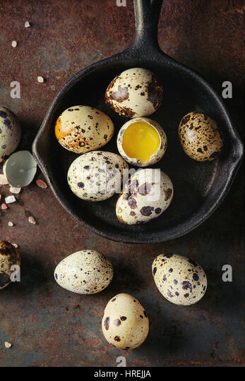 Whole and broken quail eggs with yolk in shell and pink sea salt crystal in small iron cast pan over old rusty texture - Stock Image