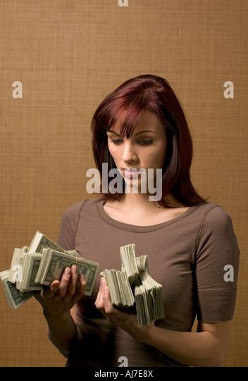 red haired 25-30 year old woman holds stacks of money in her hands - Stock Image