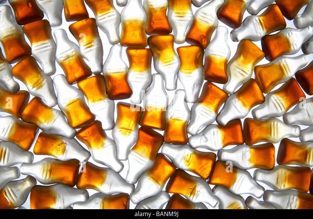 Cola bottle gummy candy on white background - Stock Image