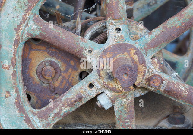 close up of corroded spokes on an example of vintage farm machinery - Stock Image