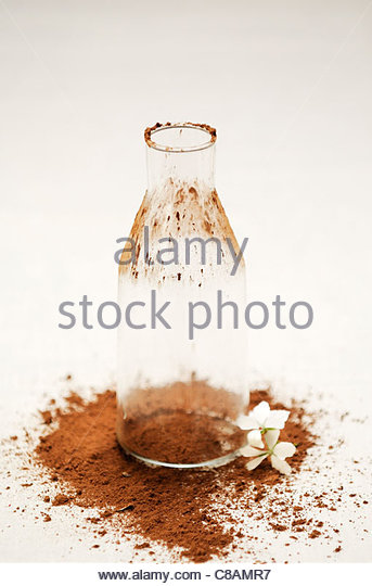 Empty bottle,cocoa and jasmin flower - Stock Image
