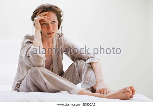 Depressed woman in pajamas sitting in bed - Stock Image