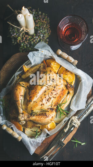 Christmas dinner with roasted whole chicken, decorative candles and wine - Stock Image