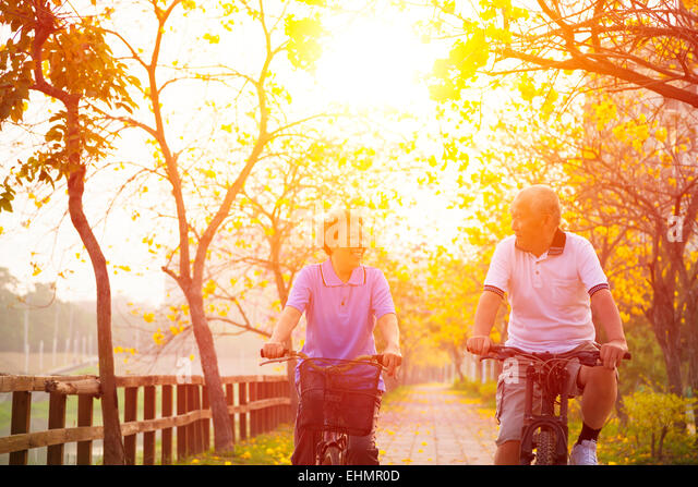 senior couple on cycle ride in the park - Stock Image