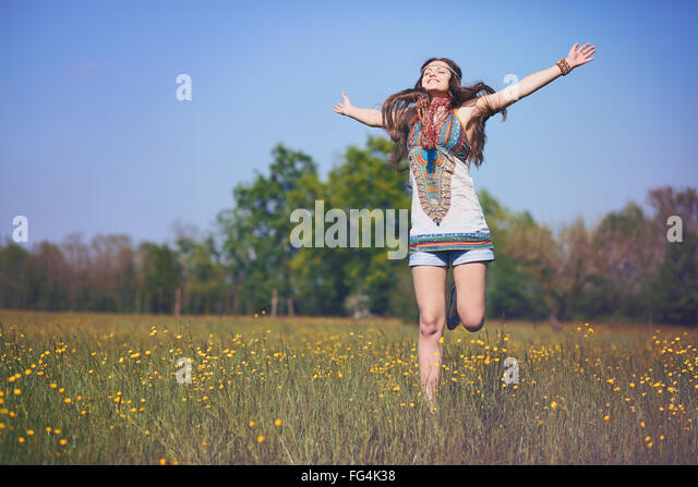 Happy and smiling hippie woman jumps in a summer field . Vintage photo effect - Stock Image