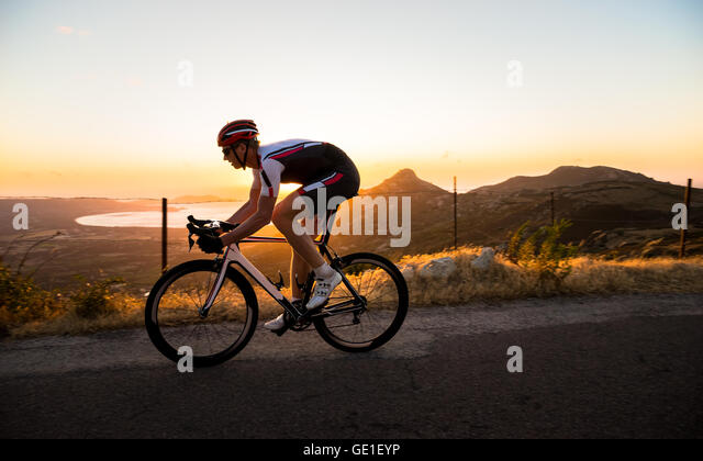 Man cycling at sunset, Corsica, France - Stock Image