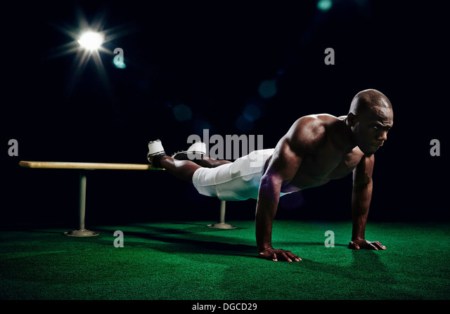 Bare chested american footballer doing press ups - Stock Image