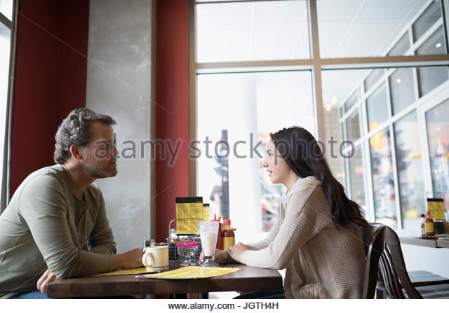 Father and teenage daughter dining at diner table - Stock Image