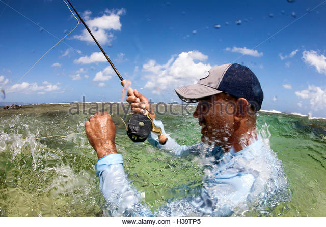 man fly fishing in salt water - Stock Image