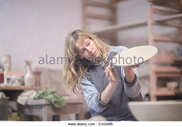 Female potter checking edge of plate in workshop - Stock Image
