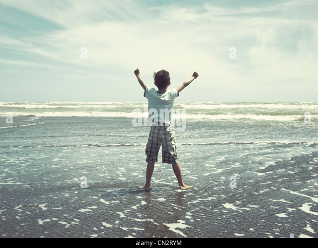 I hold back the sea: boy on beach, New Zealand. - Stock-Bilder