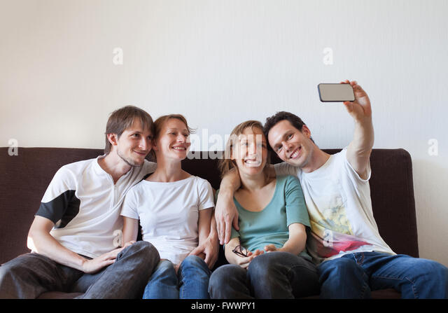group of friends taking photo of themselves, home party, selfy - Stock Image