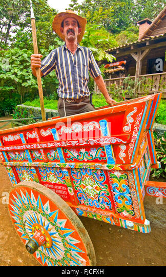 Boyero Cowboy riding his coloful handmade painted Sarchi Ox Cart, La Paz Gardens, Costa Rica - Stock Image
