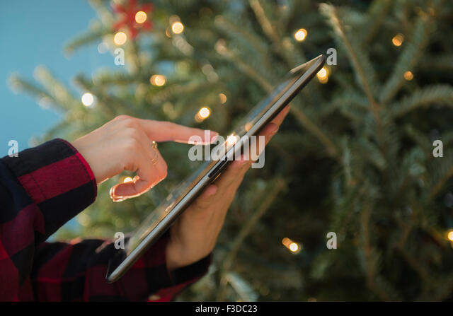 Person using tablet near Christmas tree - Stock Image