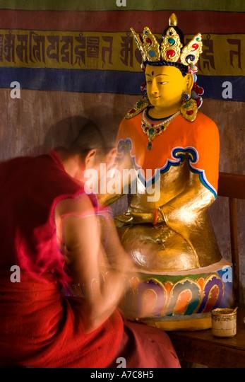 Young monk paiting a Buddha inside Thiksey Monastery Ladakh Indian Himalaya - Stock Image