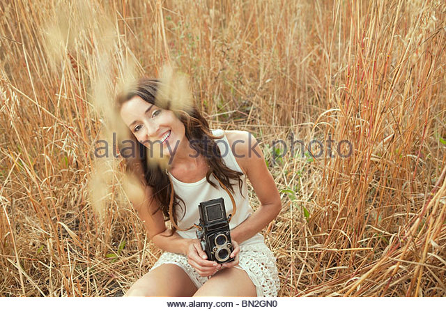 Woman in field holding old-fashioned camera - Stock Image